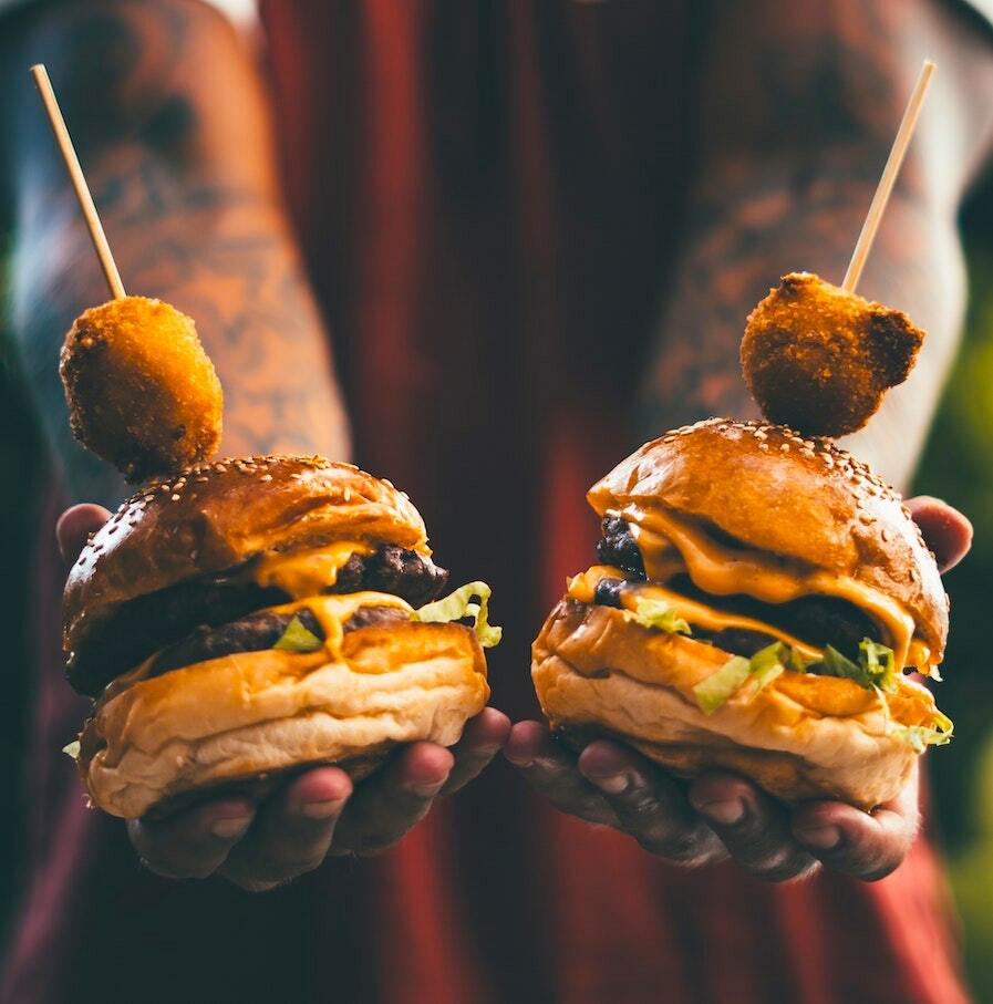 man holds up two burgers in his hands
