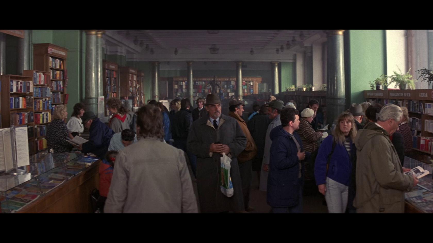 Коннери изучает ассортимент Дома книги. Из-за спины за ним наблюдает скульптурный Ленин.