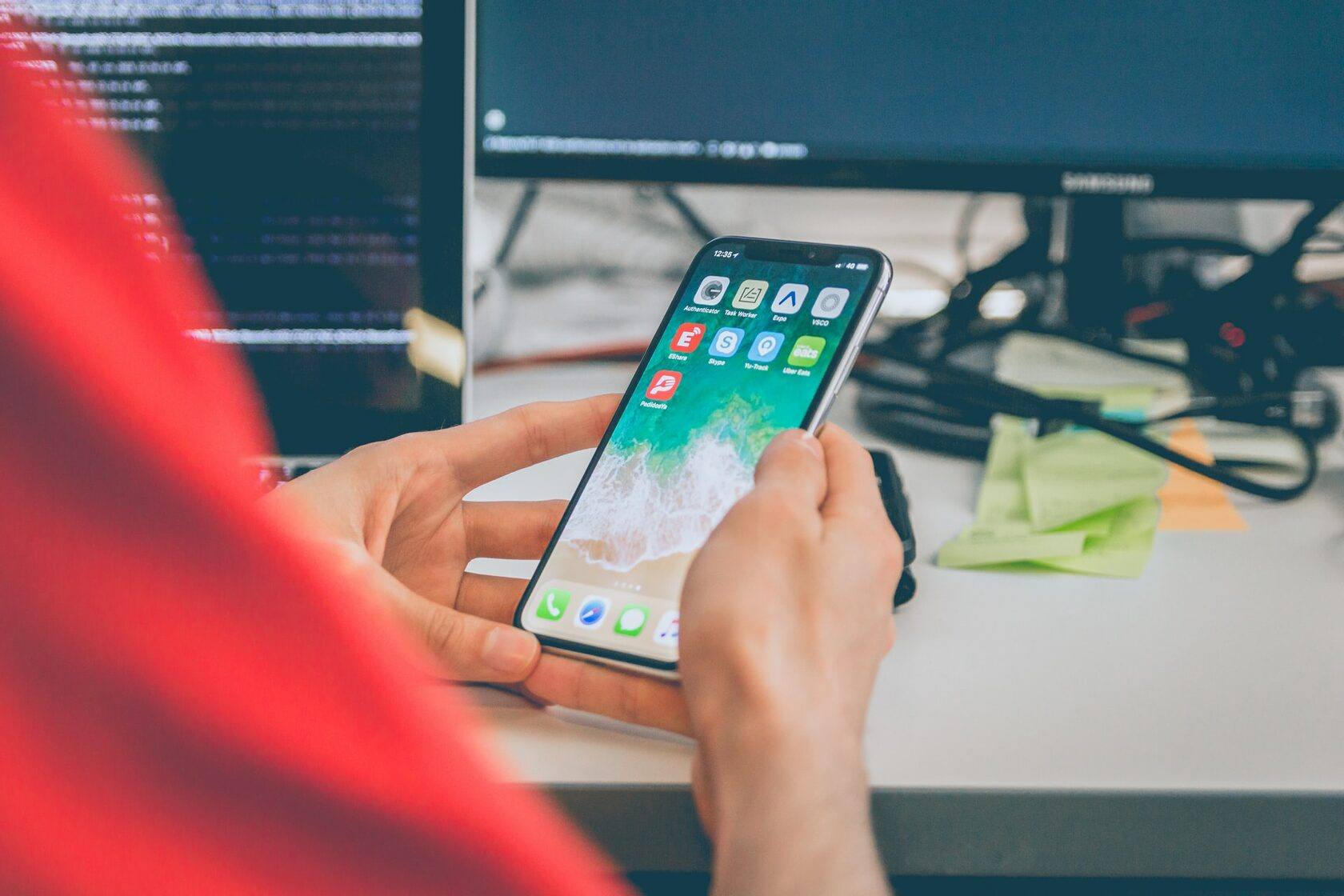 Image showing a man in an office setting holding a phone with a few no code apps on it.