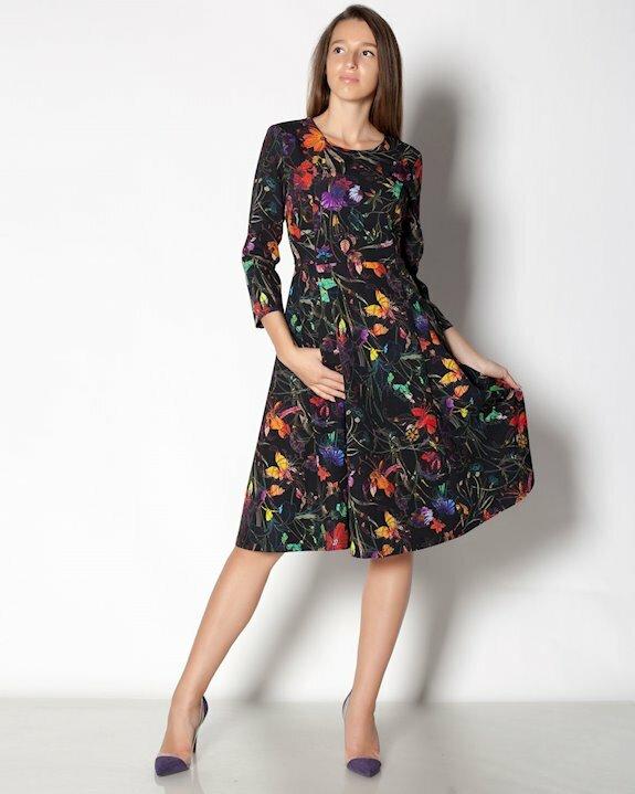Черна дамска рокля с ефектен цветен принт и разкроена долна част.