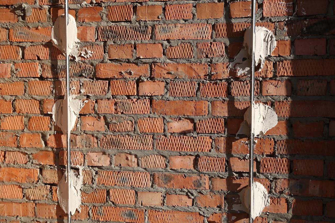 Маяки для оштукатурення стін на цегляній стіні