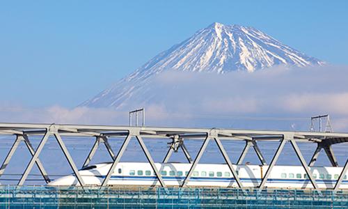 Скоростной поезд синкансен мчится на фоне горы Фудзи