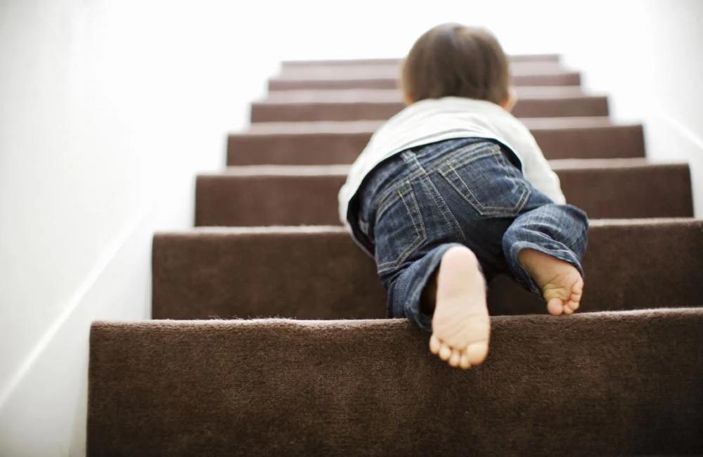Ребенок забирается по  лестнице