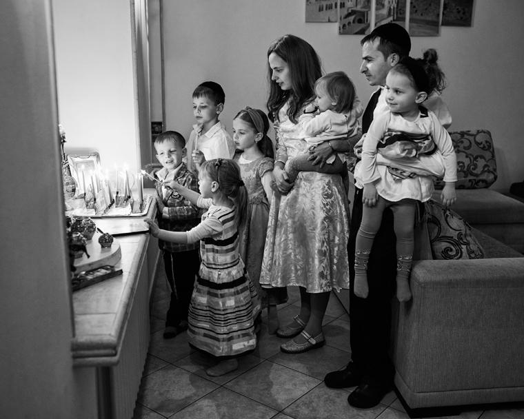 Семья зажигает ханукию. Фото Колдунова+Клёсов