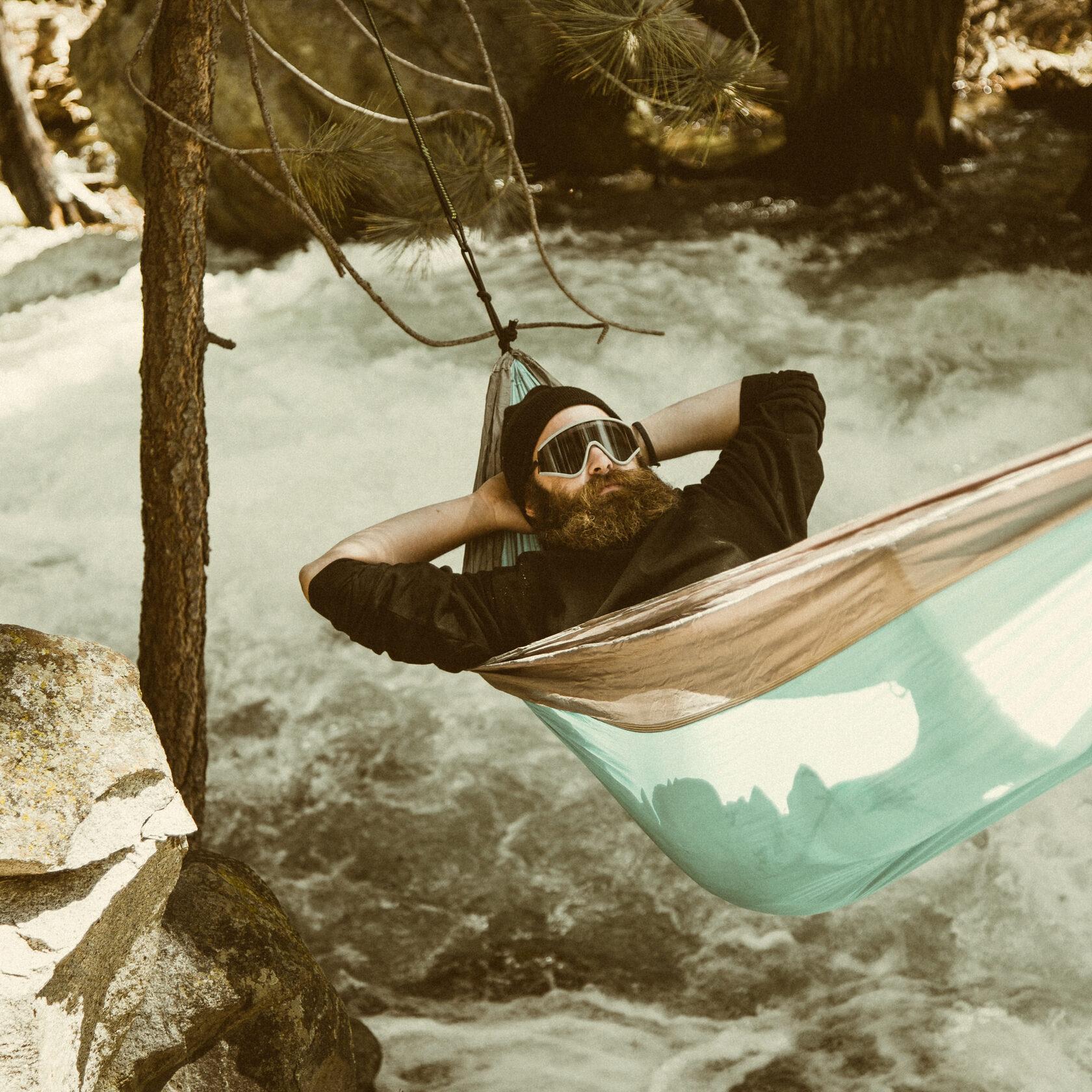a man lies in a hammock