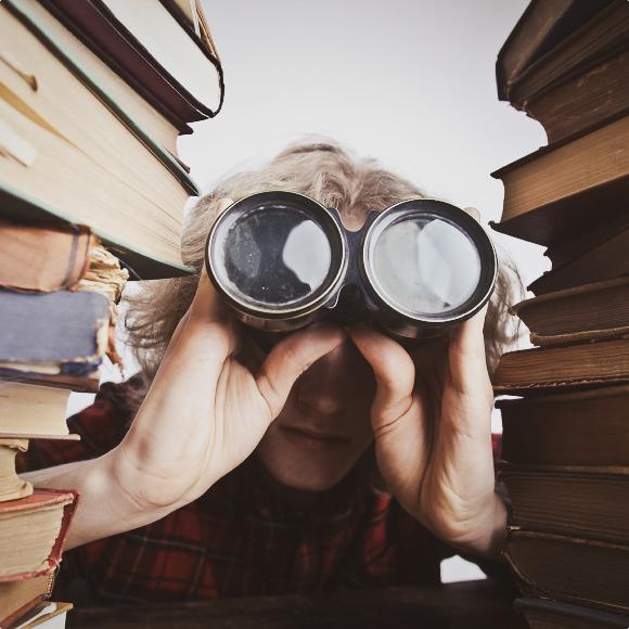 Мальчик смотрит в бинокль на учебники