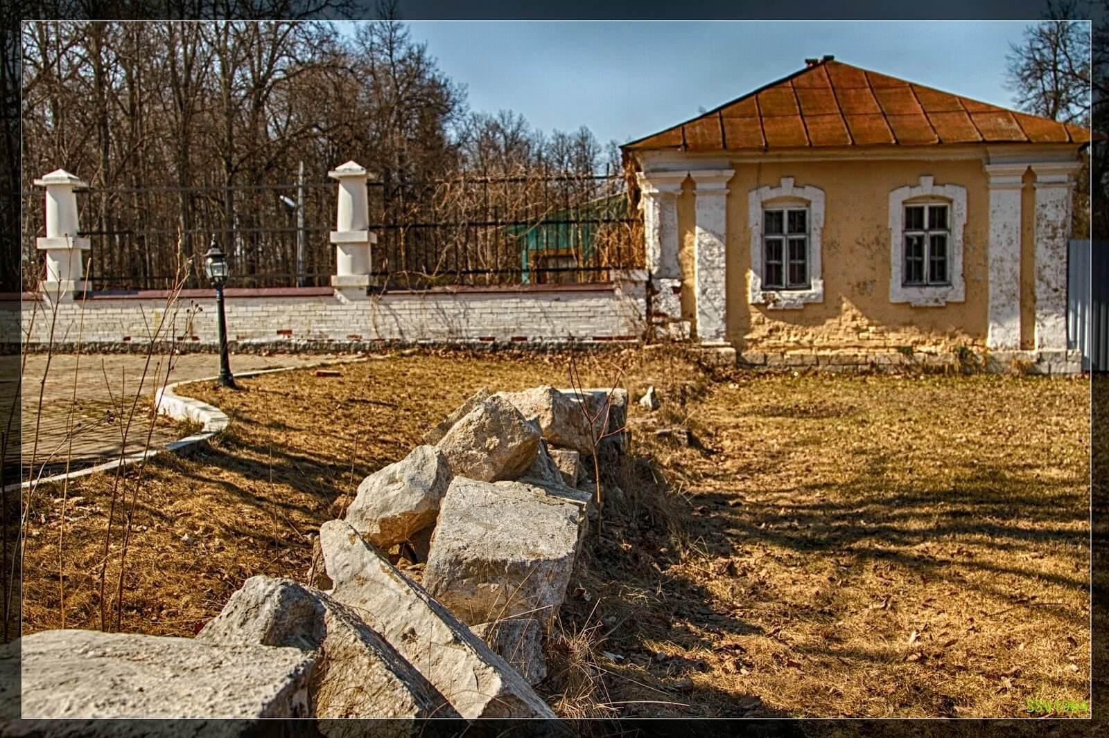 Западный флигель (дом управляющего усадьбой Дубровицы) и камни - остатки стены, выстроенной вокруг усадьбы графом Матвеем Дмитриевым-Мамоновым в 1820-х гг.