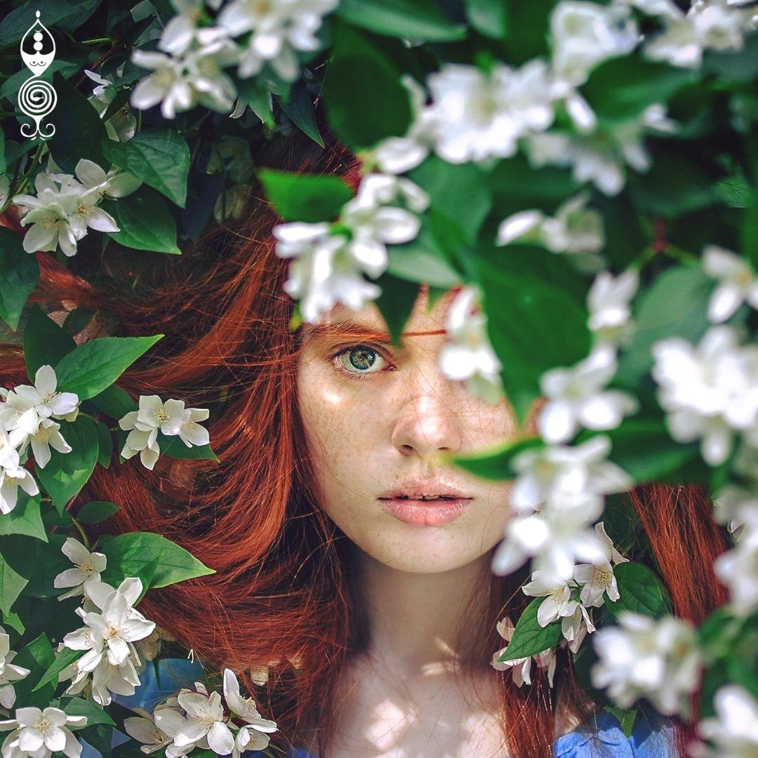 donna che guarda tra gli alberi e i fiori