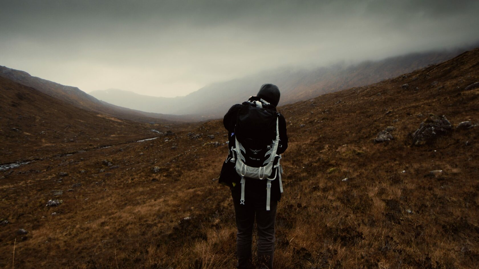 man travels with a backpack in nature