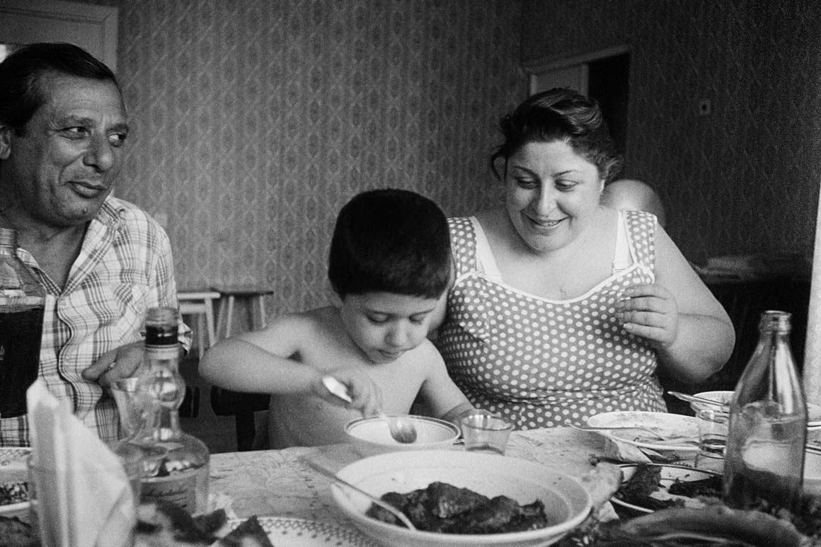 masha ivashintsova; leica; 1989; room; relatives; Tbilisi; Georgia; table; food; alcohol; barbecue; bottle; day; bright light; three; father; mother; boy; a son; close-up; portrait; Georgian; sitting; shirt; dress; dotted; bra; large breasts; plate; a family; eat; tablecloth; stool documentaryphotography sovietphotography; streetphotography; bnwphotography; magnumphotos