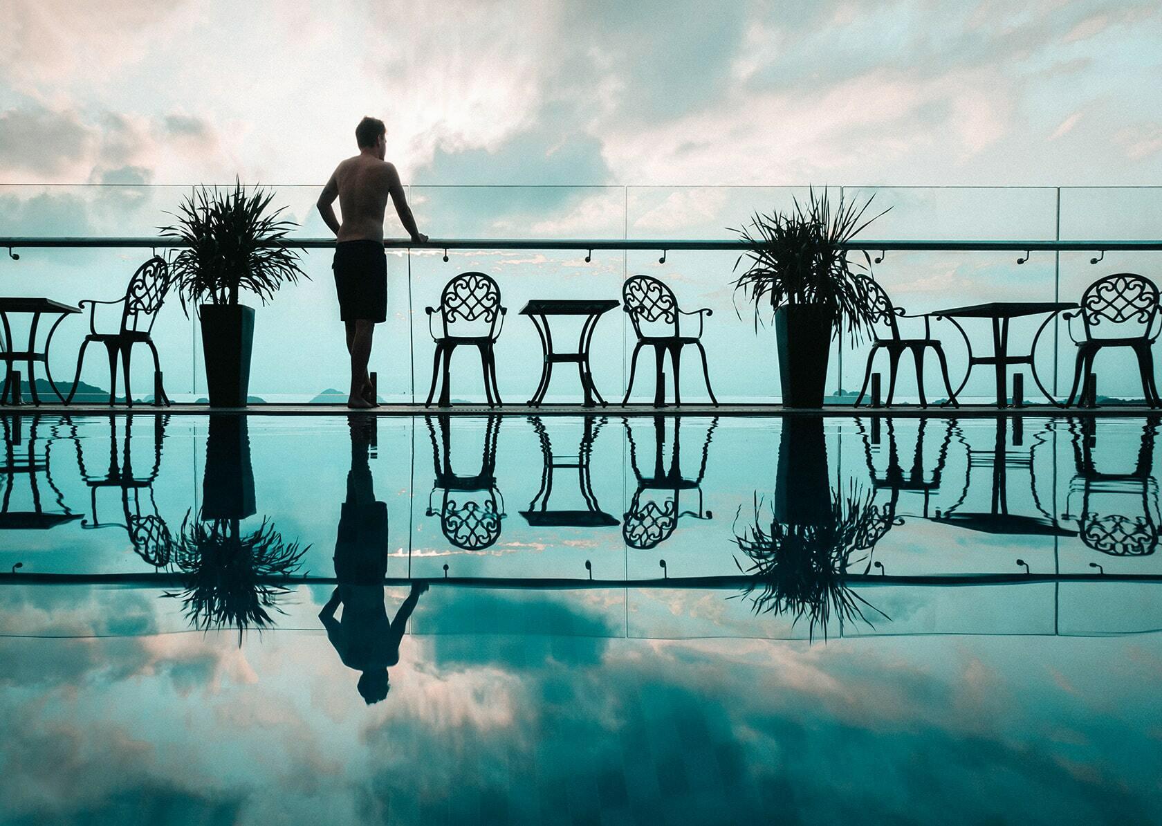 Foto van persoon bij een zwembad uitkijkend naar de zee uit fotografie collectie mensen van Simon Wijers