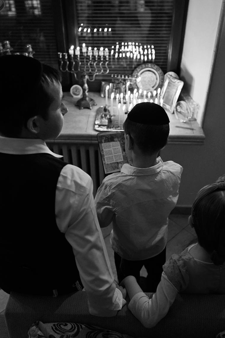 Мальчик читает молитву перед зажиганием ханукии. Фото Koldunova+Klyosov