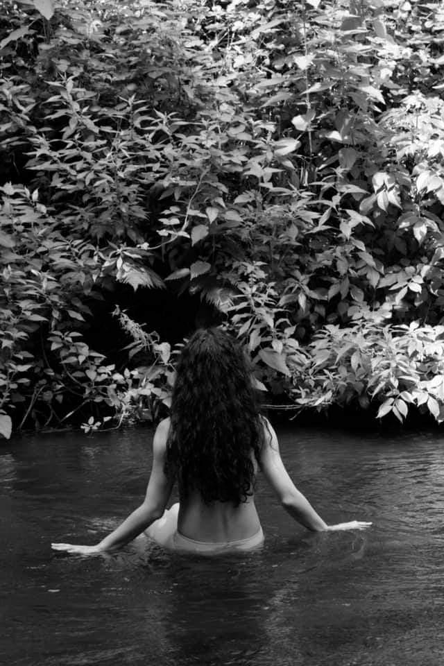 donna di spalle che fa un bagno in acqua
