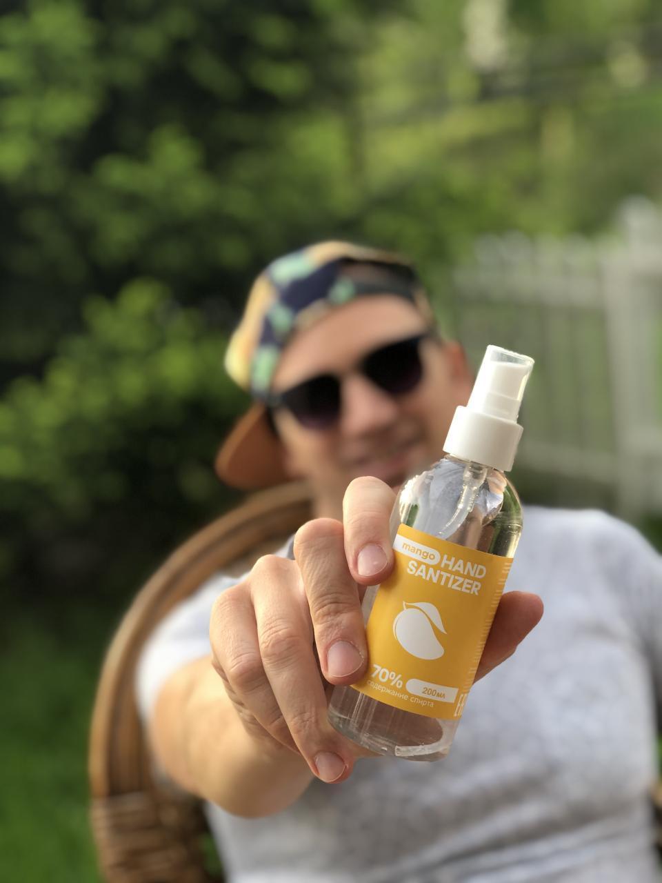 Антисептик для рук Hand Sanitizer Extra 200 мл с экстрактом манго портретно в мужской руке