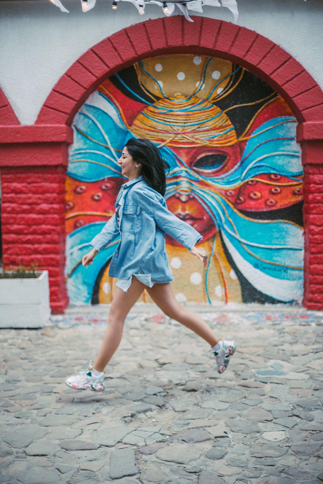 Девушка бежит на фоне граффити