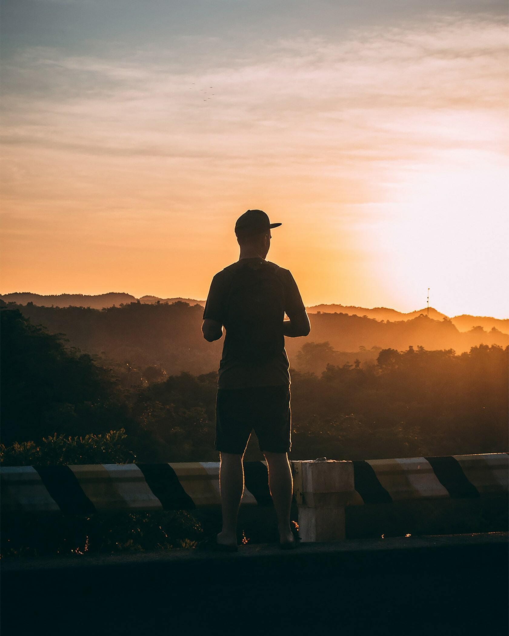 Foto van een persoon wat uit kijkt over het landschap tijdens de zonsondergang uit fotografie collectie mensen van Simon Wijers