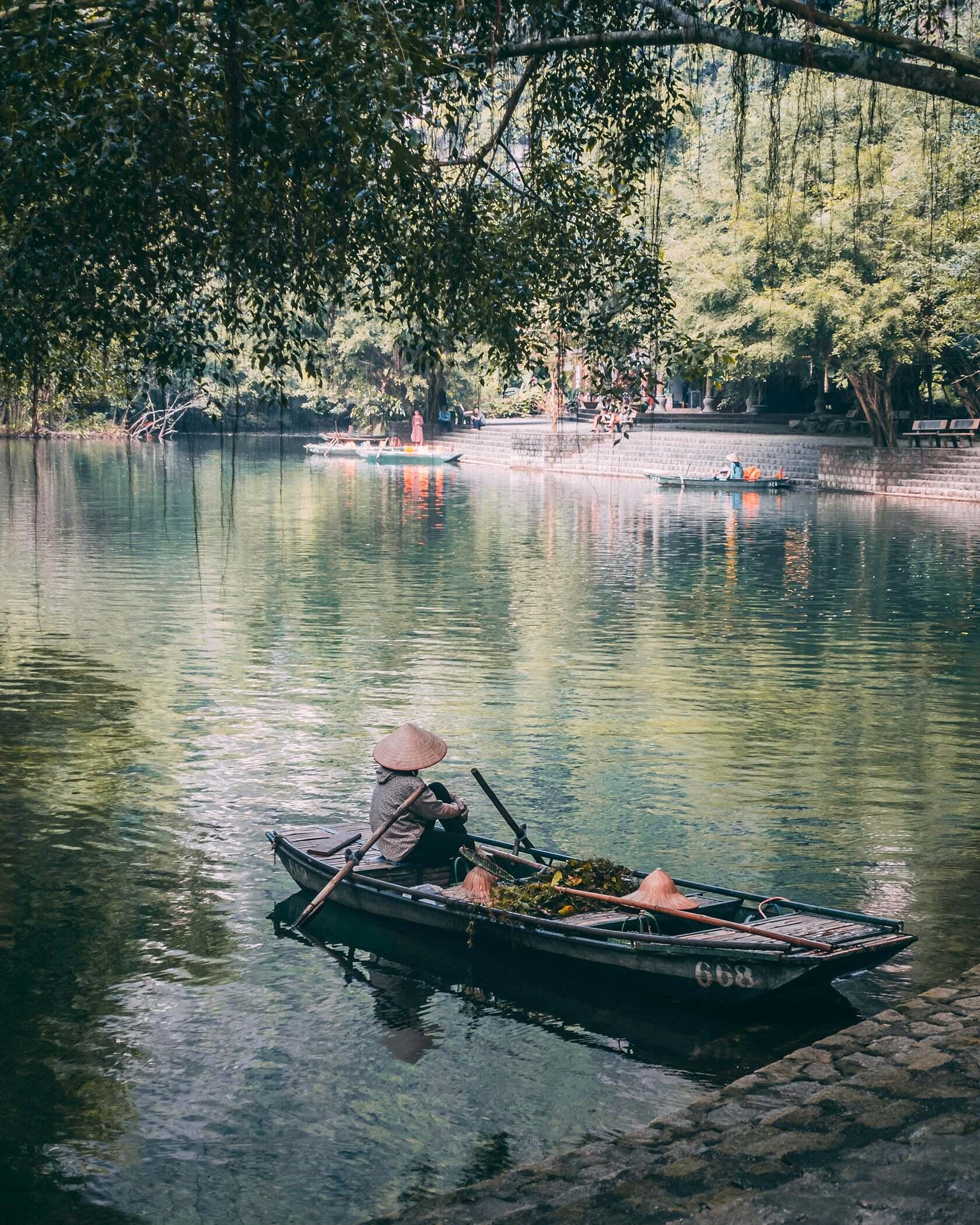 Foto van persoon in een bootje aan een groot meer in Vietnam uit fotografie collectie mensen van Simon Wijers