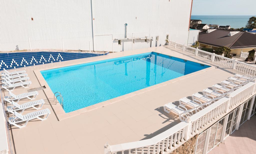 Бассейн с шезлонгами на крыше отеля Марсель - вид на море и горы