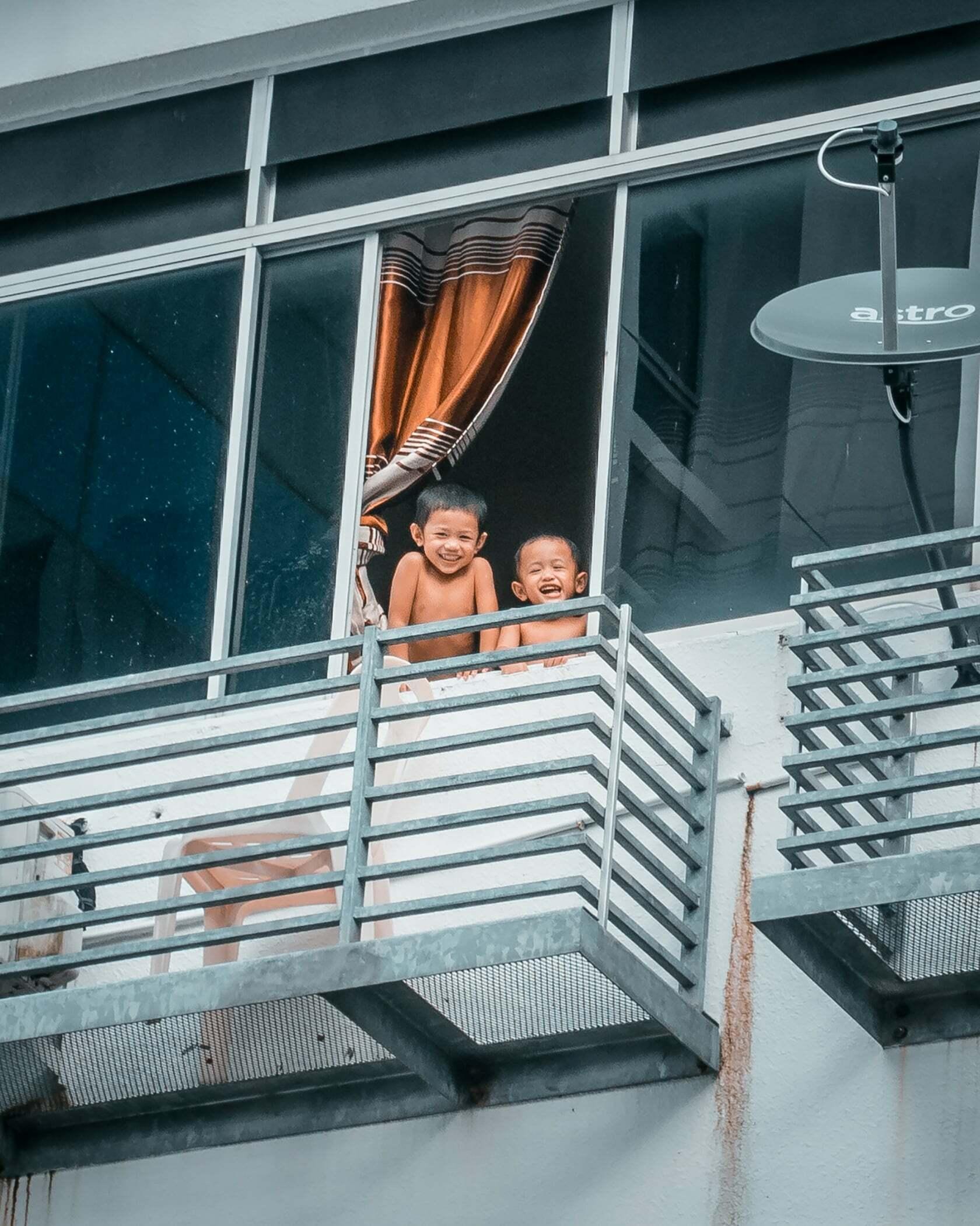 Foto van kinderen die hangen uit een raam uit fotografie collectie mensen van Simon Wijers