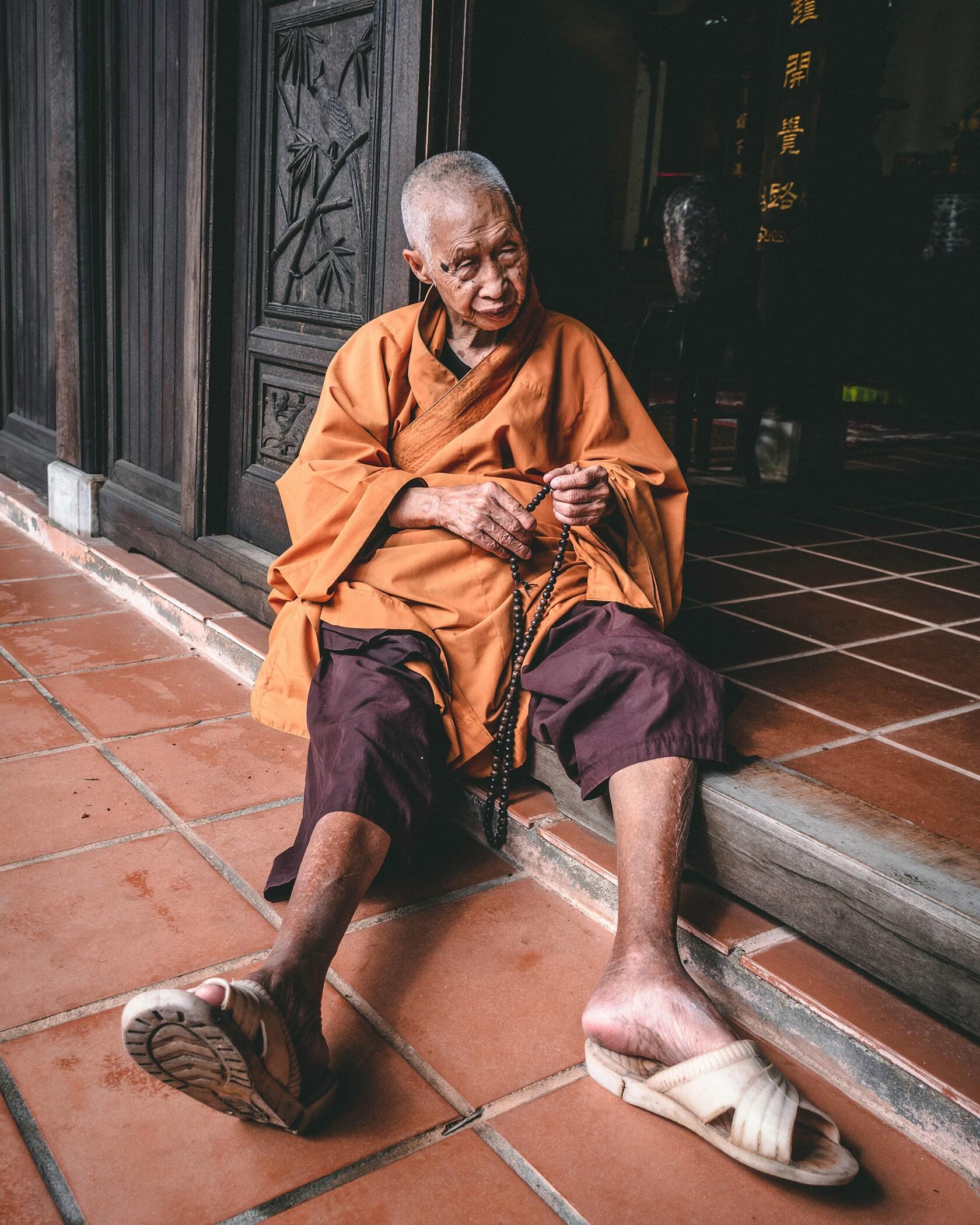 Foto van een monnik op leeftijd, zittend op de grond uit fotografie collectie mensen van Simon Wijers