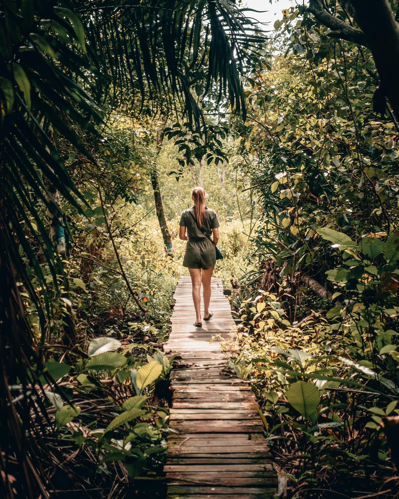Foto van persoon lopend over een houten pad in de jungle uit fotografie collectie mensen van Simon Wijers