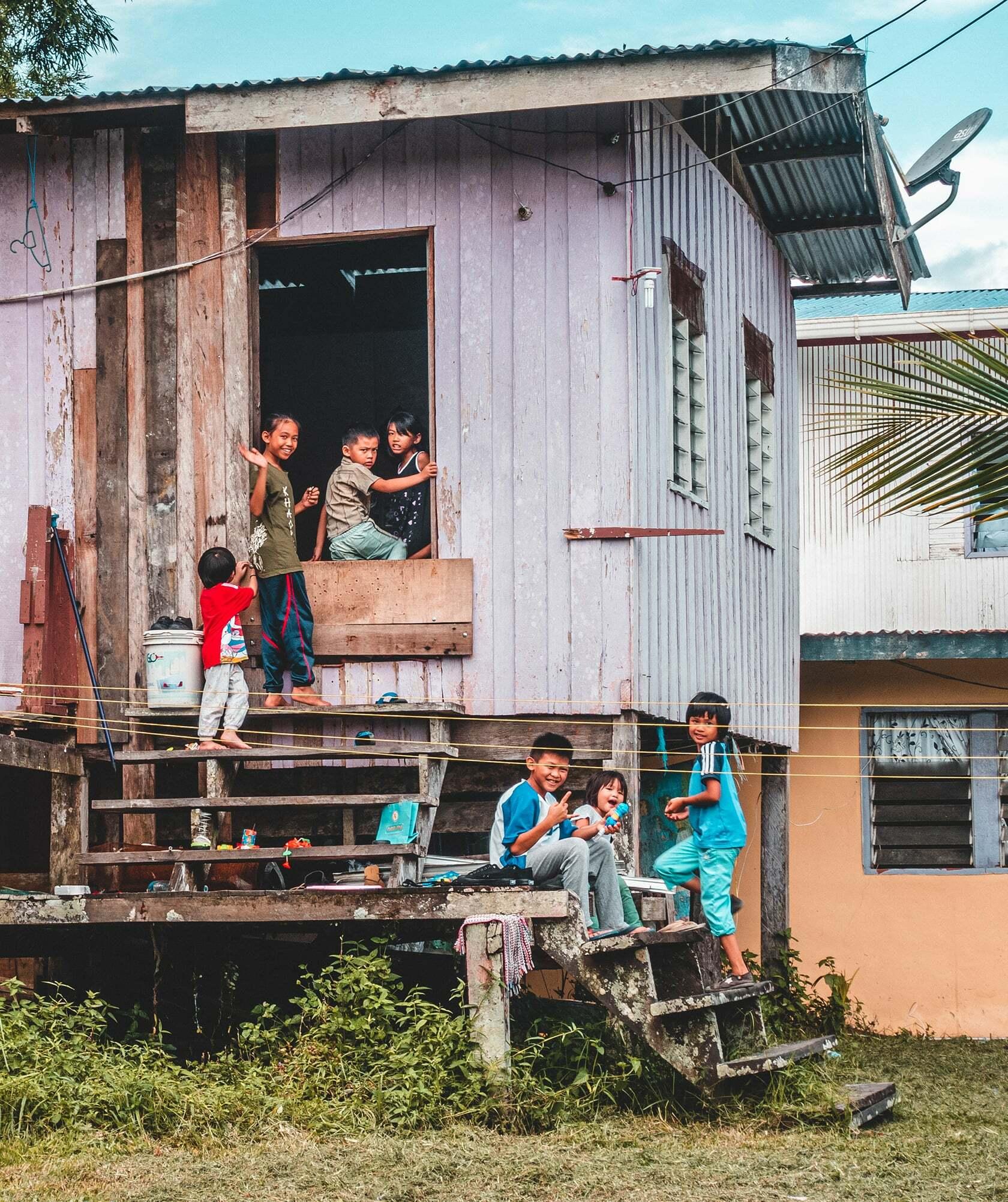 Foto van kinderen die voor het huis zitten uit fotografie collectie mensen van Simon Wijers