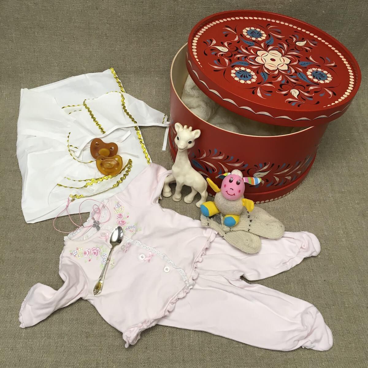 первые вещи ребенка в красном коробе, первая пустышка, первая игрушка, первый детский костюмчик