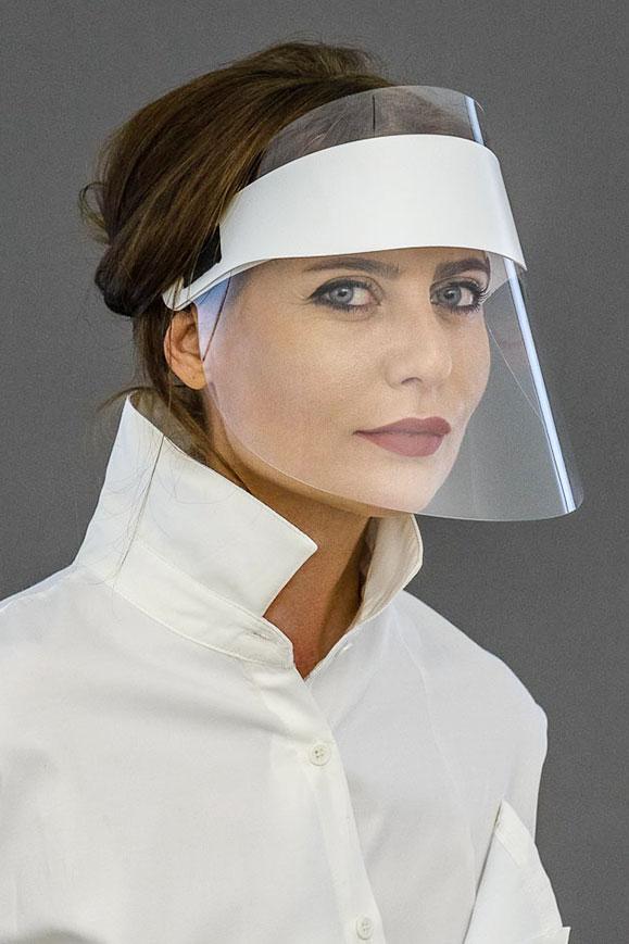 девушка в защитном щитке на лице против коронавируса COVID-19