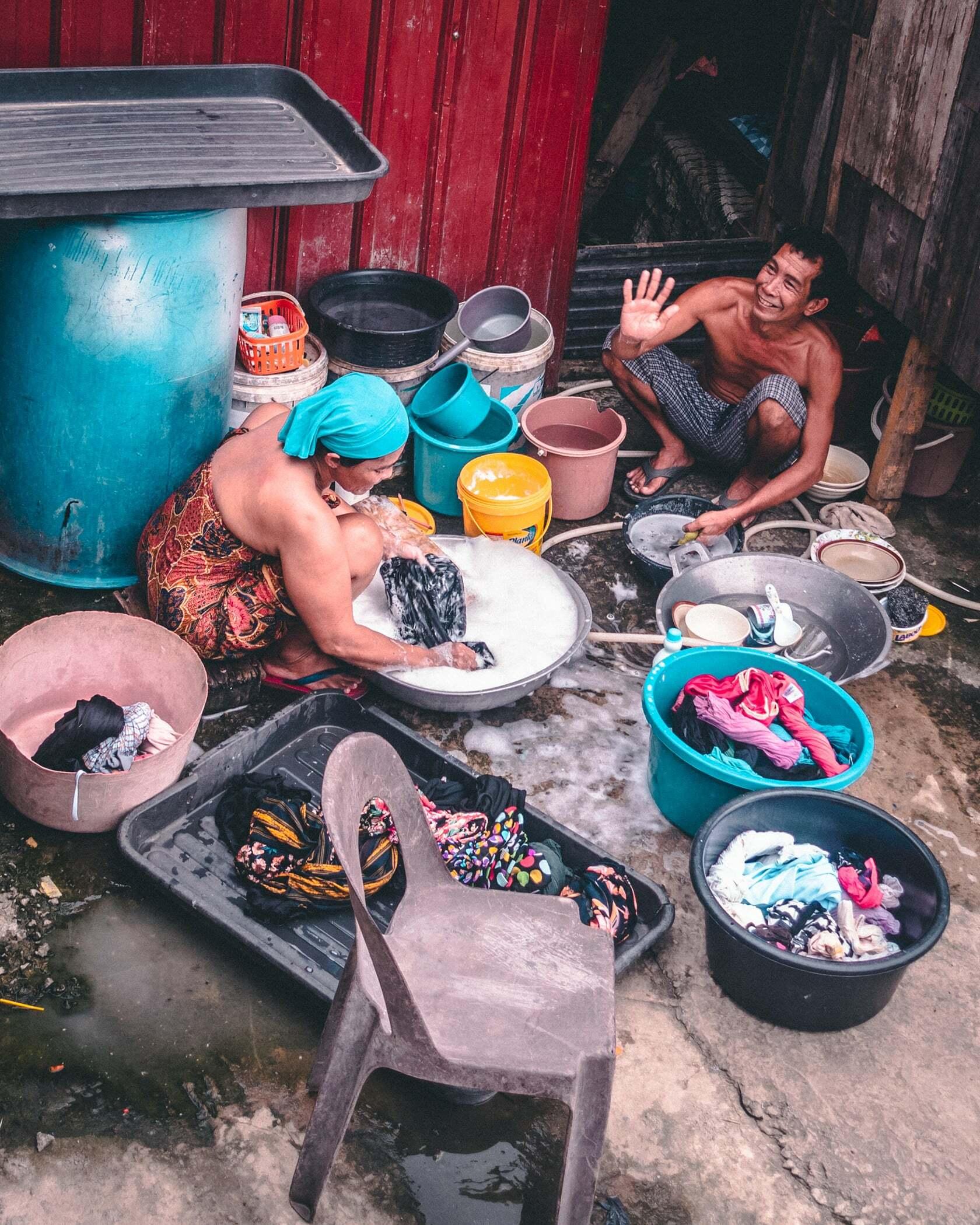 Foto van personen die de afwas aan het doen zijn in een sloppenwijk uit fotografie collectie mensen van Simon Wijers