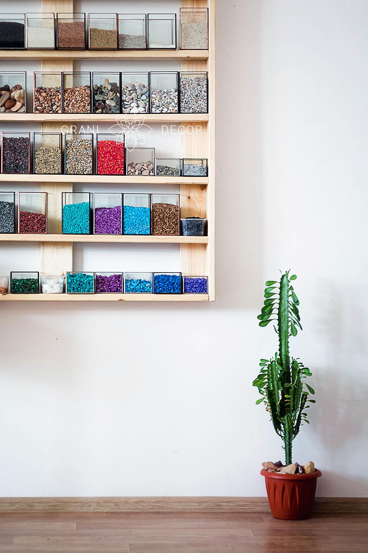 стеллаж с цветными камнями разной фракции и красивым кактусом в углу