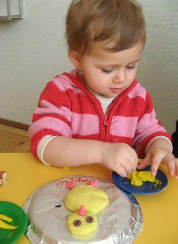Девочка лепит из пластилина в детском саду Изумруд
