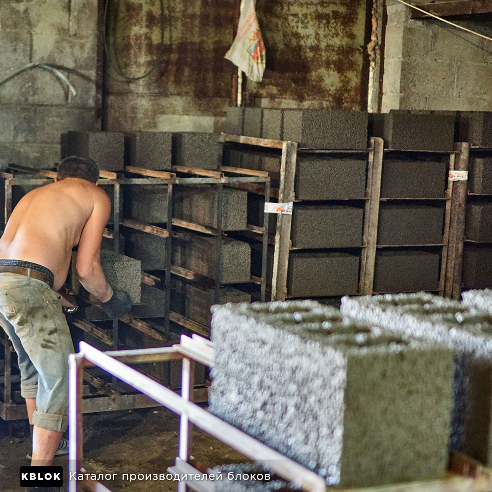 рабочий переносит блоки в сушку