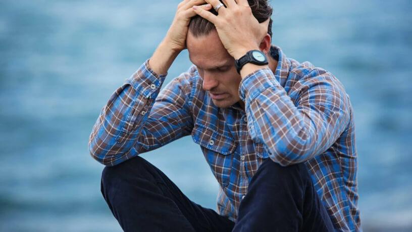 мужчина держится за голову расстроенный