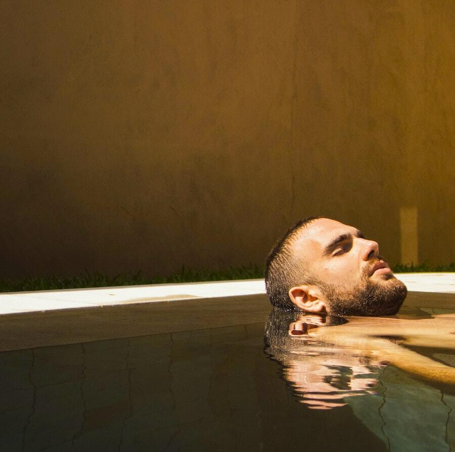 a man relaxs in a swimming pool