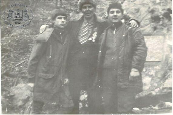 Андрей Колупов, Арман Порсугян и ветеран 76-й морской бригады А. Т. Голузов у скалы с мемориальной плитой - фото