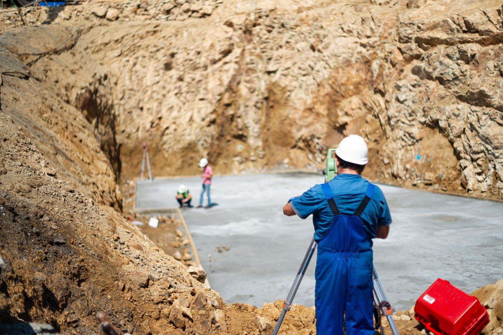 Геодезист и инженеры проводят проверку бетонного основания