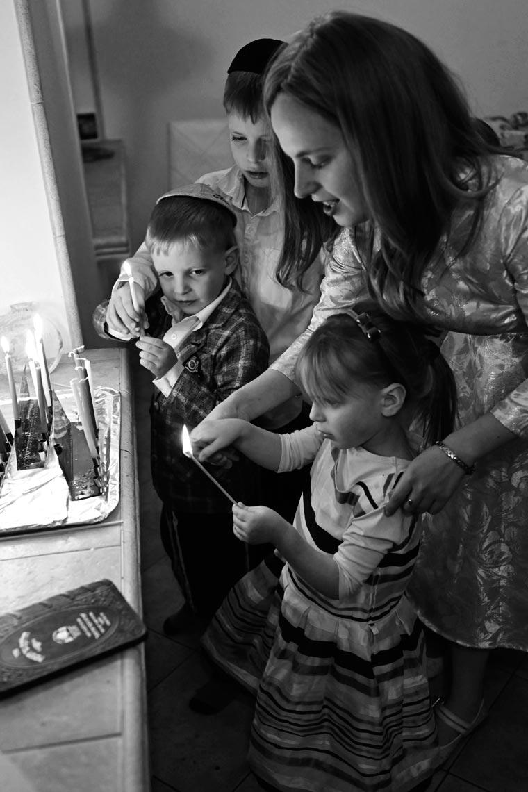 Мама помогает дочери зажечь ханукию. Фото Koldunova+Klyosov