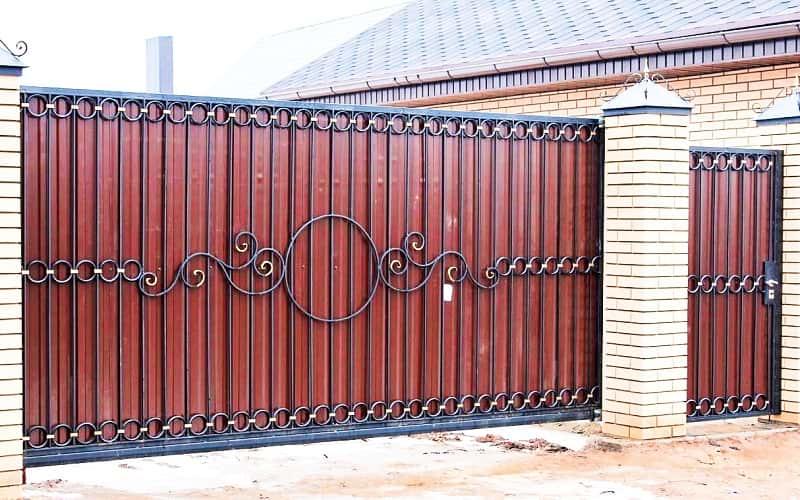Откатные ворота из профнастила с кирпичными столбами и ковкой
