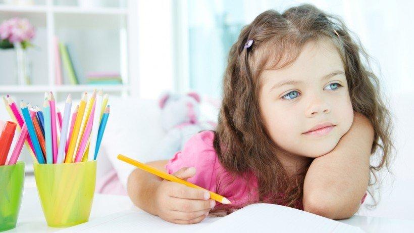 Маленькая девочка рисует карандашами