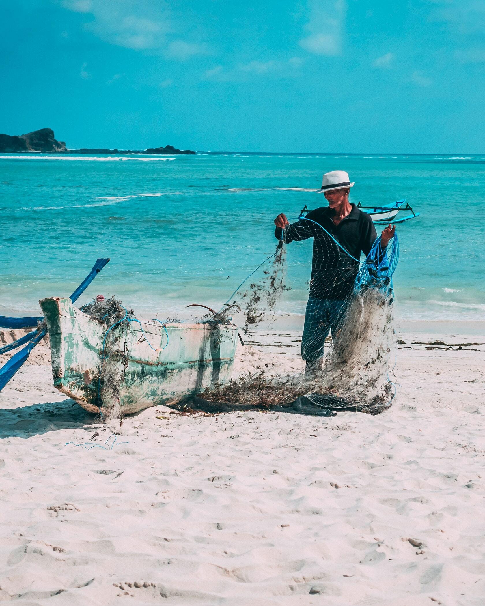 Foto van visserman aan het werk op het strand in Indonesië uit fotografie collectie mensen van Simon Wijers