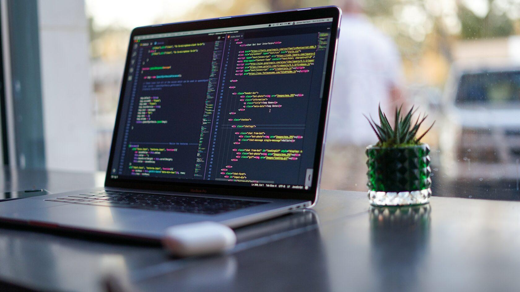 Laptop auf einem Schreibtisch vor einem Fenster