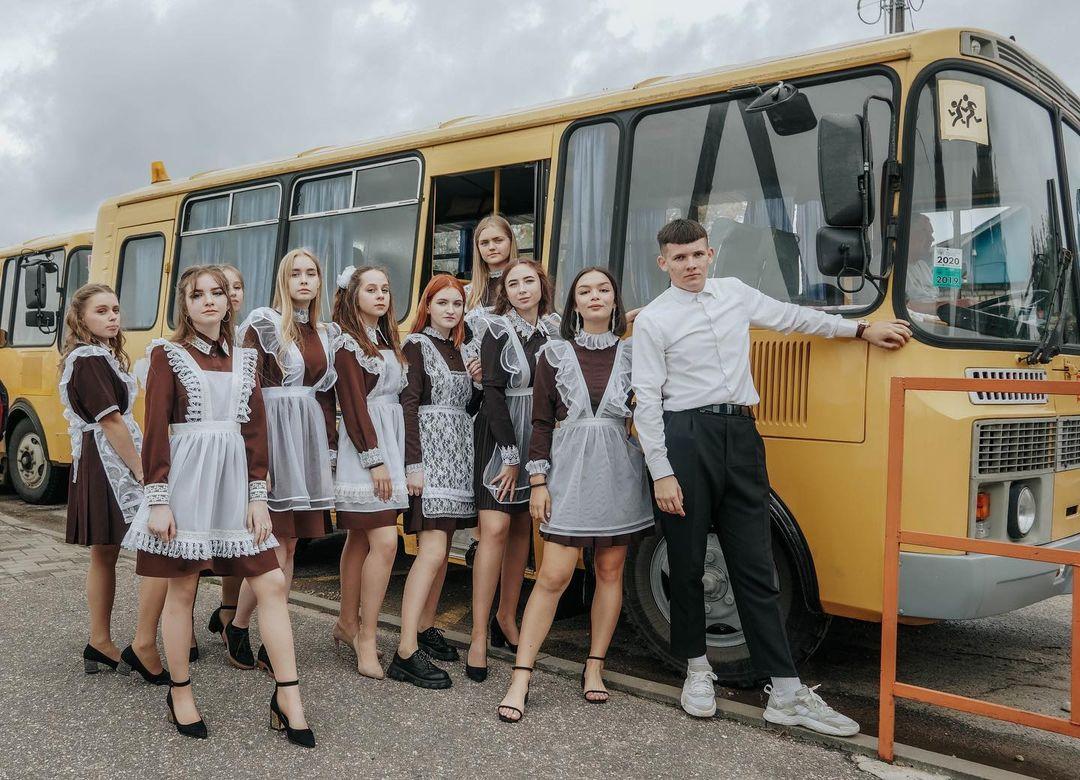 выпускники в школьной форме на фоне школьного автобуса